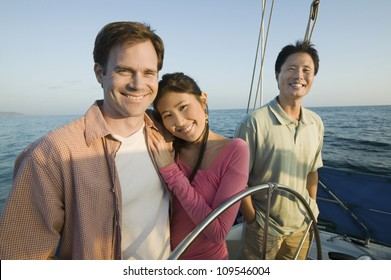 Happy loving couple with male friend on the yacht during vacation
