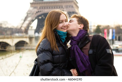 Happy loving couple near in Paris kissing near the Eiffel Tower
