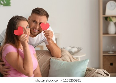 Happy loving couple with paper red hearts at home