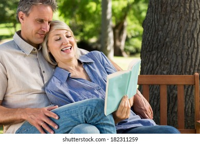 Happy loving couple reading book on park bench