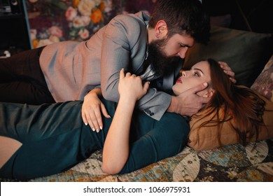 Happy loving couple relaxing on bed at home, handsome bearded man touching smiling beautiful young woman face, enjoying togetherness and tenderness in love, looking in the eyes stroking caressing