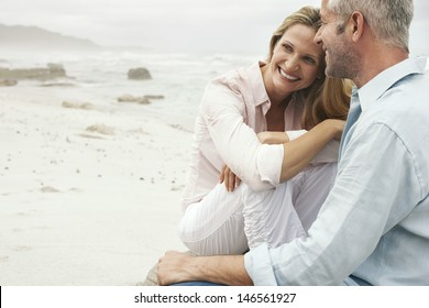 Happy loving couple sitting on beach