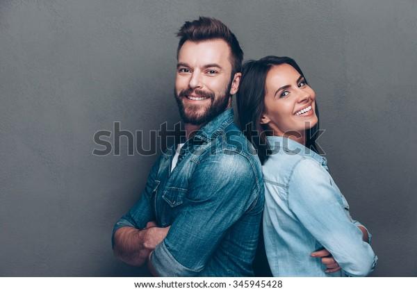 Gelukkig liefdevol stel. studio shot van mooi jong paar in jeans dragen staan terug naar terug en glimlachend