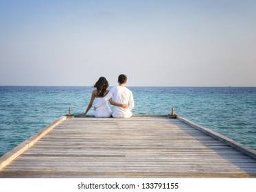 Happy loving couple in white clothes sitting on a pier on Maldives
