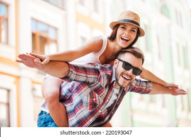 Happy loving couple. Happy young man piggybacking his girlfriend while keeping arms outstretched