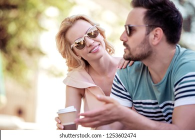 Happy loving couple.Cheerful young couple drink coffee to go and having fun outdoors.