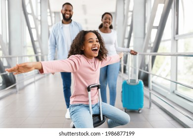 Happy Loving Family In Airport. Portrait of joyful excited black girl sitting on suitcase and laughing, spreading arms imitating plane, smiling cheerful parents walking in blurred background
