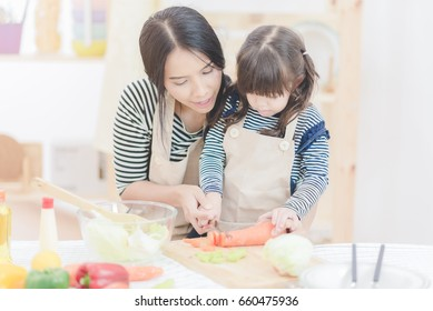 Happy loving family asian mother and her daughter prepare healthy food salad in kitchen room.Photo design for family, kids and happy people concept.