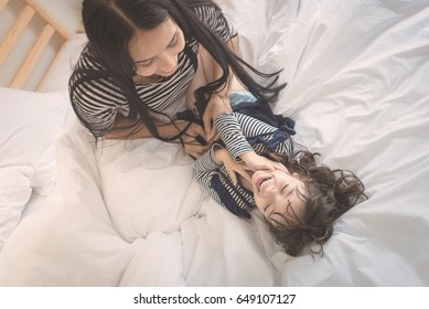 Happy loving family, asian young mother playing with her daughter in kid's room. Photo design for family, kids and happy people concept.