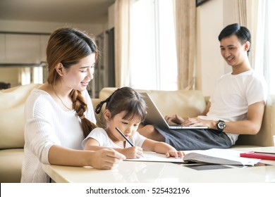 happy loving family, beatiful yong mother help her daughter do her homework at home, happy asian family concept