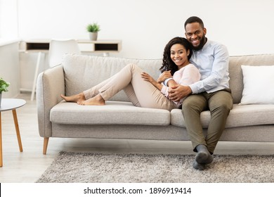 Happy Loving Family. Beautiful african american man and woman cuddling and relaxing on the couch at home in living room, smiling couple looking at camera and posing, enjoying weekend time together