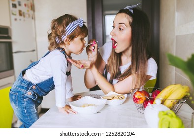 Happy loving family. Beautiful young mother feeding her cute baby girl with a spoon at kitchen.