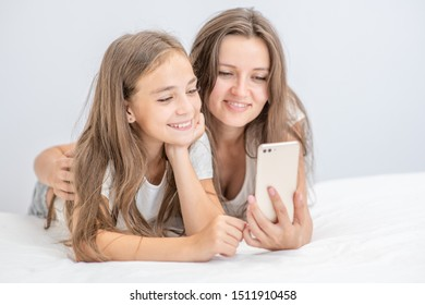 Happy loving family. Beautiful young woman and her little daughter are using a smartphone and smiling while lying in bed at home