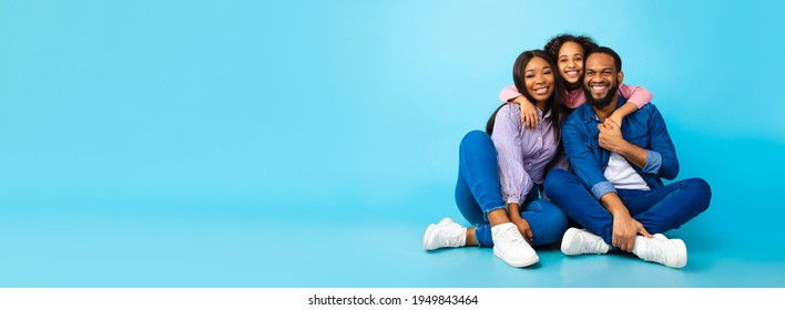 Happy Loving Family. Black man, woman and girl sitting on the floor isolated on blue studio wall. Smiling daughter emracing her mum and dad from behind, posing at camera, banner, panorama, copy space