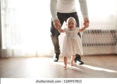 Happy loving family. Father and his daughter child girl first step. happy childhood and support of relatives concept. lifestyle and real interior