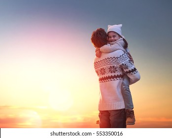 Happy loving family! Father and his daughter are playing and hugging outdoors. Cute little girl and daddy on snowy winter walk in nature. Concept of frost winter season.