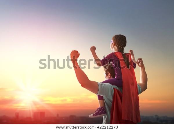 Feliz familia amorosa. Padre y su hija jugando afuera. Papi y su hija disfrazadas de superhéroe. Concepto del Día del Padre.