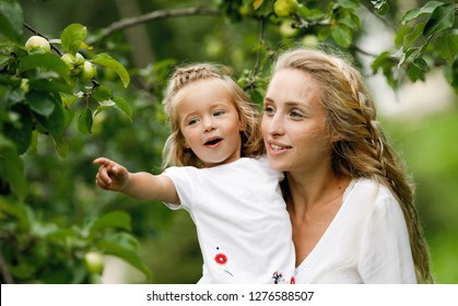 Happy and loving family in the garden. Positive and beautiful young mother blonde is holding her little cheerful daughter pointing at an apple while camping. Childhood. Summertime. Lifestyle. Summer