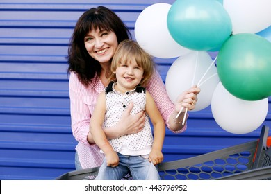 Happy loving family. Grandmother And Granddaughter playing, hugging in a Store