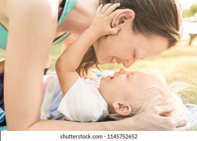 Happy loving family. Mother and child boy playing, kissing and hugging outdoors.