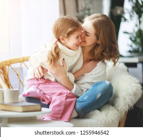 happy loving family mother and child daughter hugging by the window