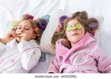 Happy loving family. Mother and children are doing hair and having fun. Mother and daughter are put cucumbers on eyes sitting on the bed in the bedroom.