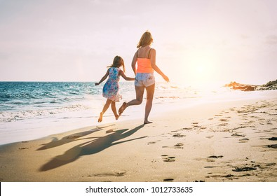 Happy loving family mother and daughter running and having fun on the beach at sunset - Mum playing with her kid next to ocean during holidays - Parent, vacation, family lifestyle concept