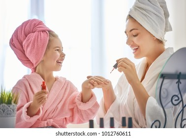 Happy loving family. Mother and daughter are doing manicures and having fun sitting at dressing table at home. Mom and child girl are in bathrobes and with towels on their heads.