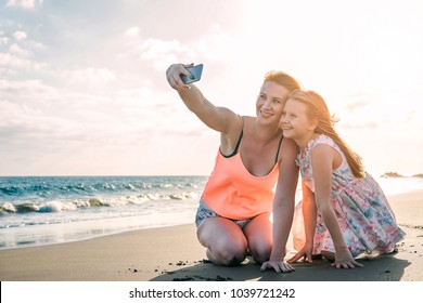Happy loving family mother and daughter taking a selfie with mobile smart phone on the beach at sunset - Mom with her kid in holiday - Parent, vacation, tech and family lifestyle concept