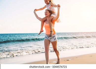 Happy loving family mother and daughter having fun on the beach in vacation - Mom carrying on shoulders her kid and running next to ocean - Holidays, parent, maternal love concept