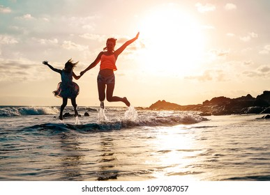 Happy loving family of mother and daughter jumping in the water at sunset on the beach - Mom with her kid having fun together on a summer day - Concept of parents summer vacations