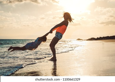 Happy loving family mother and daughter having fun on the beach at sunset - Mum playing with her kid next see in holidays - Concept of lifestyle family, parents and vacation