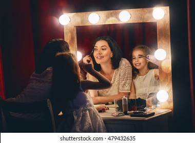 Happy loving family. Mother and daughter are doing makeup and having fun. Mother and daughter sitting at dressing table and looking at the mirror.