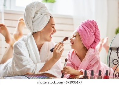 Happy loving family. Mother and daughter are doing make up and having fun. Mom and child girl are in bathrobes and with towels on their heads.