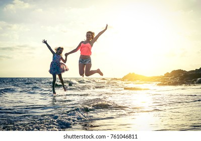 Happy loving family of mother and daughter jumping in the water at sunset on the beach - Mom with her kid having fun together on a summer day - Summer, travel, vacation and family concept