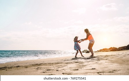 Happy loving family mother and daughter having fun on the beach at sunset - Mum playing with her kid next see in holidays - Parent, vacation, family lifestyle concept