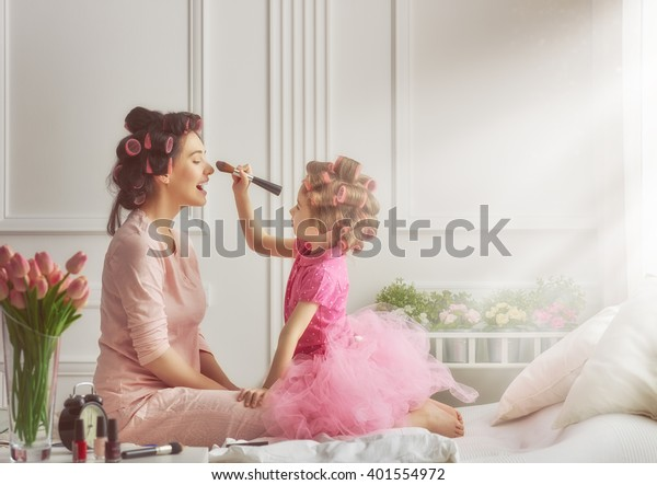 Happy loving family. Mother and daughter are doing hair and having fun. Mother and daughter doing your makeup sitting on the bed in the bedroom.