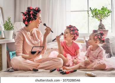 Happy loving family. Mother and daughters are doing hair and having fun. Mom and children doing makeup sitting on the bed in the bedroom.