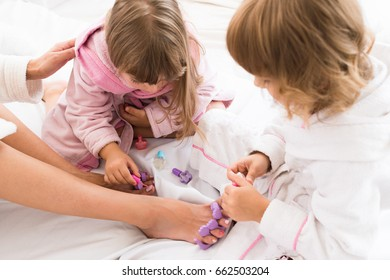Happy loving family. Mother with daughters are doing hair and having fun. Mother and children doing your pedicure on the bed in the bedroom.