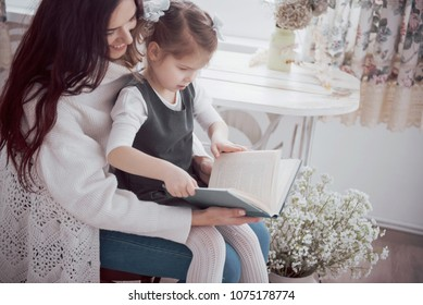 Happy loving family. Mother and her daughter playing together and reading book.