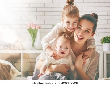 Happy loving family. Mother and her daughters children girls playing and hugging.