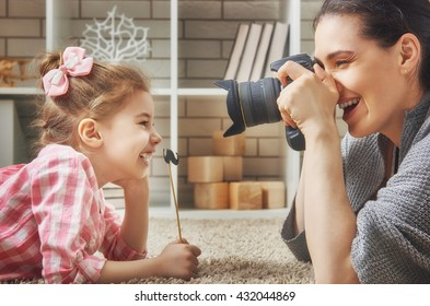 Happy loving family. Mother and her daughter child girl playing and making photo.