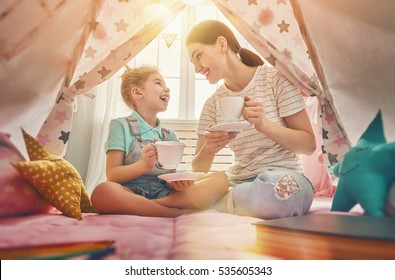 Happy loving family. Mother and her daughter girl play tea-party and drink tea from cups in children room. Funny mom and lovely child having fun indoors.