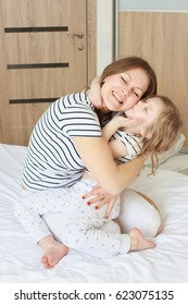 Happy loving family. Mother and her daughter child girl playing and hugging in bed at home