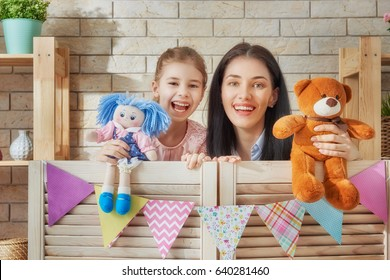 Happy loving family. Mother and her daughter in kids room. Funny mom and lovely child having fun and playing performance in the puppet theater indoors. Doll and teddy bear.