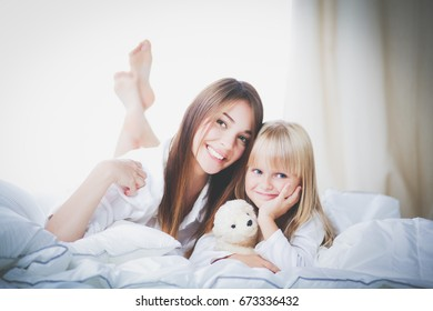 Happy loving family. Mother and her daughter child girl playing in bed