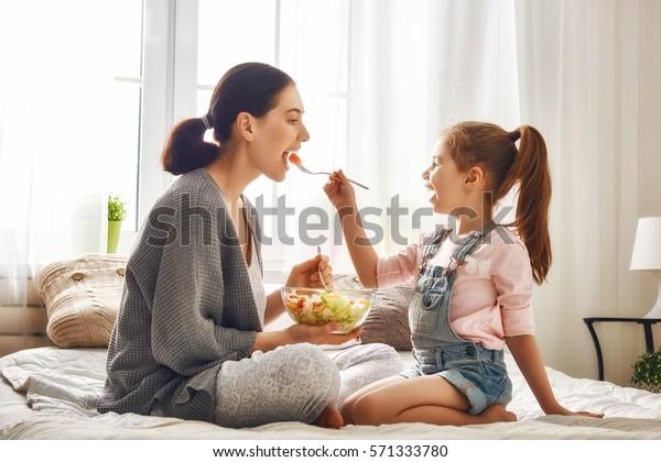 Bonne famille aimante. Mère et sa fille mangent de la salade sur le lit dans la pièce.