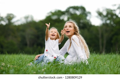 Happy and loving family in nature. Emotional and cheerful young blonde mother with her little laughing little daughter watching the rainbow sitting on the grass against a background of trees. Summer