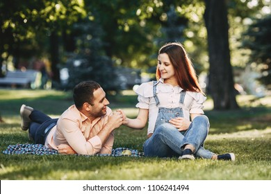 Happy loving family photo. Lovely couple expecting a baby enjoy time together outdoors. Pregnancy, maternity, motherhood, fatherhood, expectation, love, happiness concept