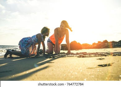Happy loving family playing on the beach during a magnificent sunset - Mother and daughter having fun enjoying time together and drawing in the sand - Parent, childhood and maternal love concept